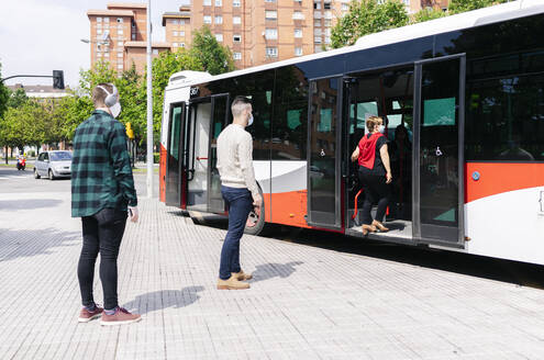 Passengers wearing protective masks  getting into public bus, Spain - DGOF01015