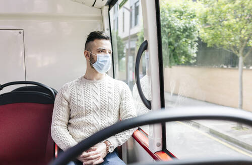 Portrait of young man wearing protective mask sitting in public bus looking out of window, Spain - DGOF01042