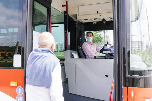 Bus driver wearing protective mask talking to passenger at bus stop, Spain - DGOF01051