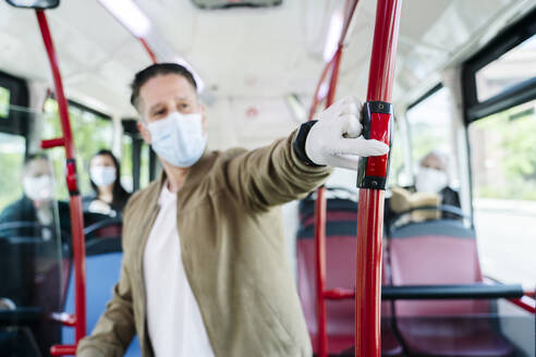 Man wearing protective mask and gloves in public bus pressing stop button, Spain - DGOF01063