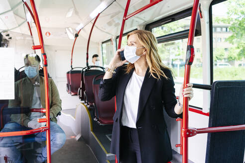 Businesswoman on the phone wearing protective mask in public bus, Spain - DGOF01078