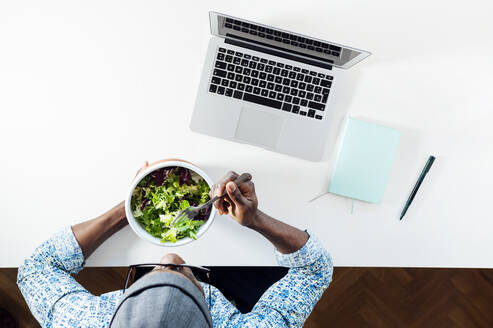 Young man eating salad while sitting with laptop at home office desk - JCMF00776