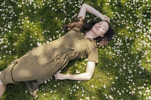 Woman enjoying her free time while lying on grass with daisies - MFF05704