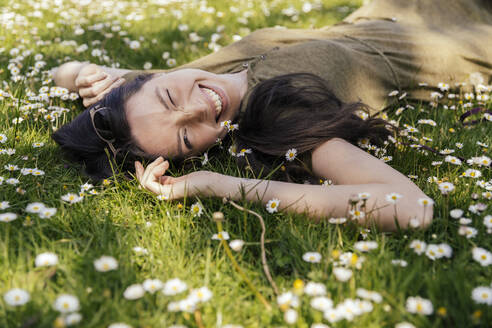 Happy woman enjoying her free time while lying on grass with daisies - MFF05707