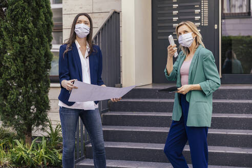 Two real estate agents wearing face masks while inspection outdoor area of house - MFF05713