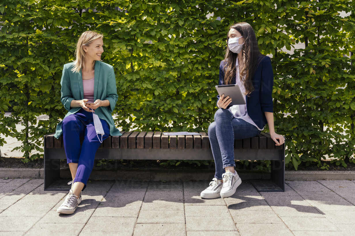 Two businesswomen sitting on bench outside and keeping their distance while wearing face mask - MFF05725 - Mareen Fischinger/Westend61