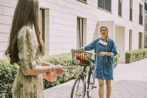 Two women with bicycle and face mask meeting in urban area - MFF05731