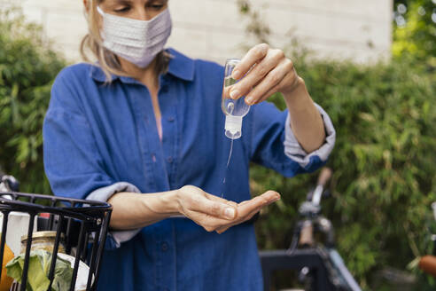 Woman with bicycle wearing face mask disinfecting her hands - MFF05737