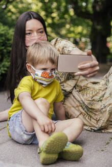 Mother and son taking a selfie while wearing face masks - MFF05746