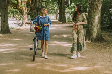 Two women with bicycle and face mask walking in park - MFF05749
