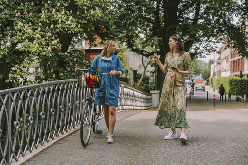 Two women with bicycle and face mask walking on a bridge - MFF05752