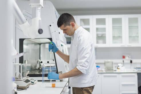 Lab worker taking dye from beaker using long pipette - OCAF00527
