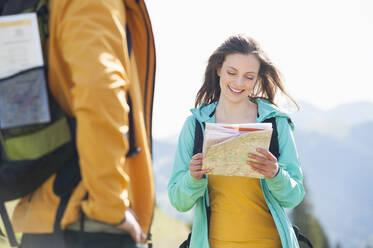 Smiling woman looking at map, Wallberg, Bavaria, Germany - DIGF11658