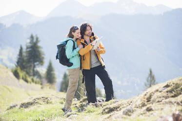 Hiking couple looking at map, Wallberg, Bavaria, Germany - DIGF11661