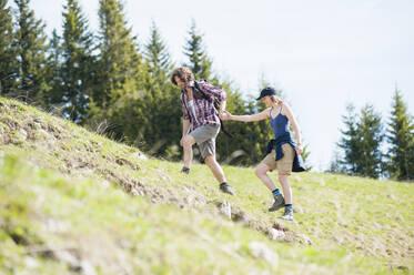 Hiking couple on meadow in summer, Wallberg, Bavaria, Germany - DIGF11670