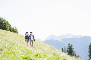 Hiking couple on meadow in summer, Wallberg, Bavaria, Germany - DIGF11673