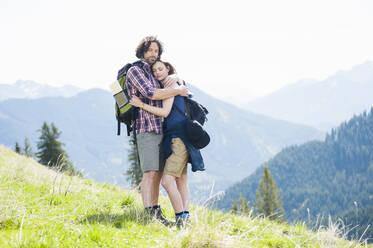 Hugging couple on meadow in summer, Wallberg, Bavaria, Germany - DIGF11676
