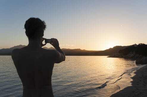 back view of man taking photo of sunset with cell phone, Sardinia, Italy - DIGF11733