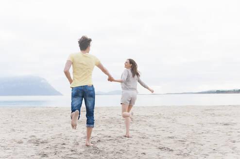 Happy couple running hand in hand on the beach, Sardinia, Italy - DIGF11739