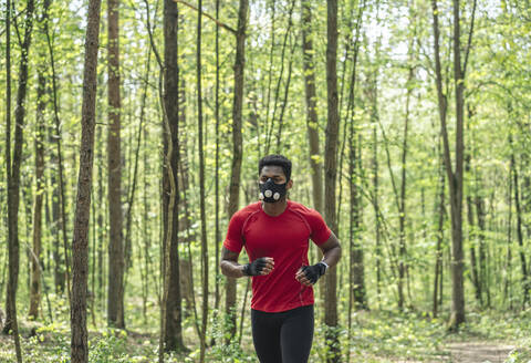 Sportsman wearing face mask running in the forest - AHSF02696