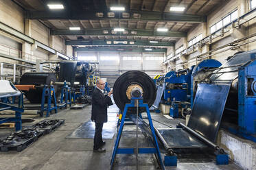 Senior businessman examining product in a rubber processing factory - DIGF11864