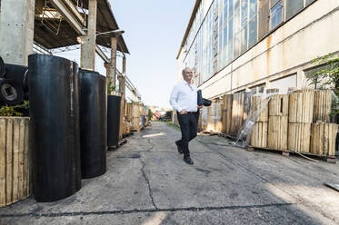Senior businessmanwalking on yard of a rubber processing factory - DIGF11873