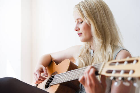 Portrait of blond woman playing guitar - DIGF12011