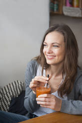 Portrait of smiling woman drinking smoothie in a coffee shop looking at distance - DIGF12026