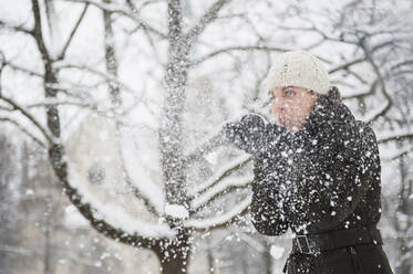 Woman blowing snowing from her hands - DIGF12029