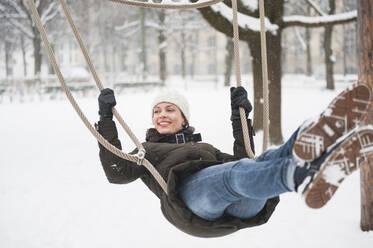 Portrait of happy woman on swing in winter - DIGF12032