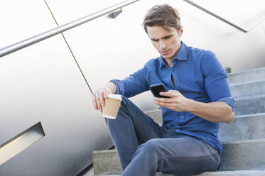 Businessman holding coffee using smart phone while sitting on steps - DIGF12050