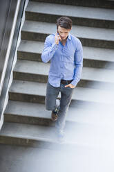 Businessman talking over smart phone while moving down on steps - DIGF12053