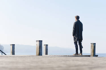 Man looking at lake against clear sky while standing on pier during sunny day - DIGF12056