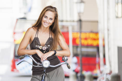 Portrait of smiling woman leaning on handlebar in the city - DIGF12071