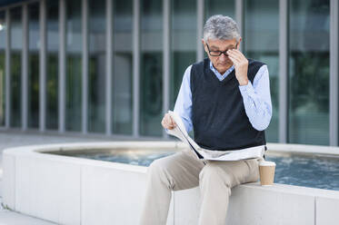 Senior businessman with coffee to go reading newspaper outdoors - DIGF12077