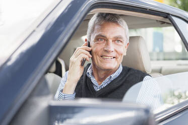 Portrait of smiling senior businessman on the phone in car - DIGF12083