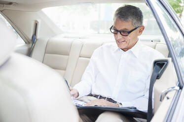 Smiling senior businessman working on back seat of car - DIGF12086