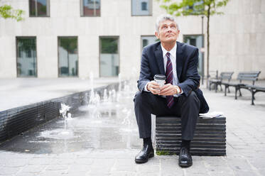 Portrait of senior businessman having a break with coffee to go outdoors - DIGF12092