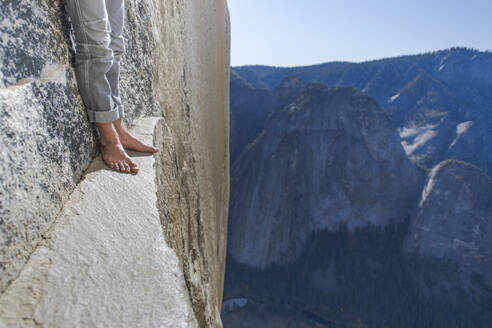 Man standing on a ledge, view of bare foot, very high El Capitan - CAVF82214