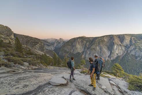 Three hikers looking at Half Dome from El Capitan sunset Yosemite - CAVF82253