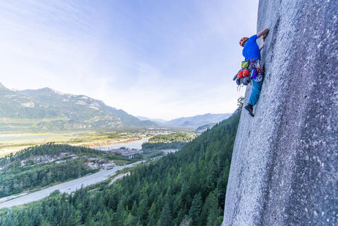 Man lead climbing granite Squamish with background view of valley - CAVF82328