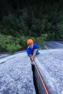 Man smiling and looking up at camera while climbing off width Squamish - CAVF82331