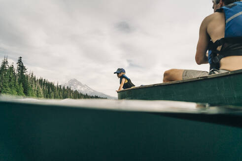 A young girl rides in a canoe with her dad on Lost Lake in Oregon. - CAVF82574