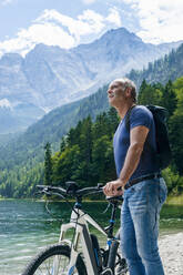 Senior man with e-bike at Eibsee lakeside - DIGF12135
