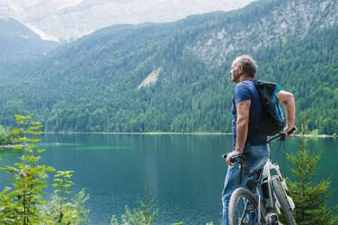 Senior man with e-bike enjoying view over Eibsee - DIGF12141