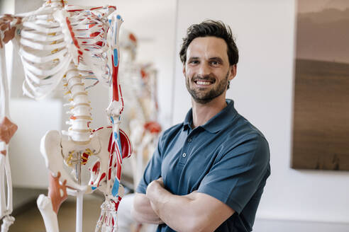 Physiotherapist standing by anatomical skeleton with arms crossed - DAWF01547