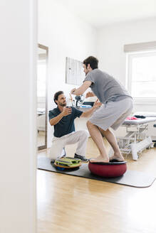 Physiotherapist assisting patient, practicing on balance trainer - DAWF01574