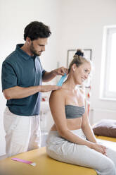 Physiotherapist applying therapeutic tape on patient's neck - DAWF01580