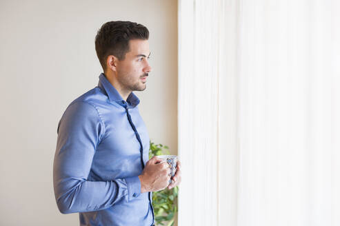 Thoughtful man holding coffee mug while standing by window at home - DIGF12151