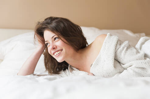 Thoughtful young woman smiling while lying in bed at home - DIGF12160
